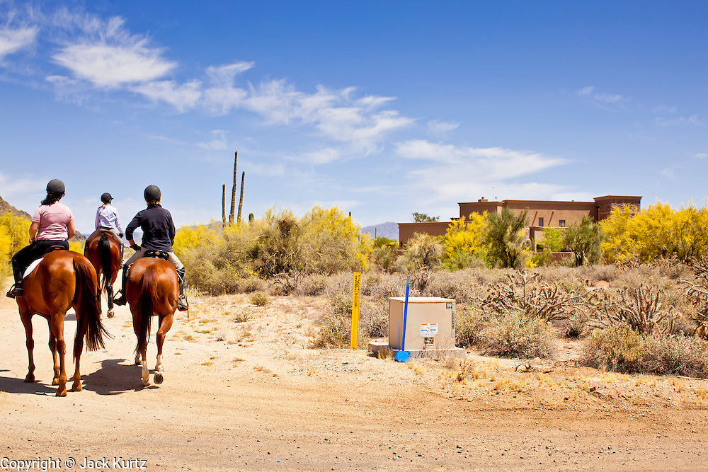 """22 MAY 2011 - SCOTTSDALE, AZ:  People on horseback pass a home (on the right) reportedly owned by Sarah Palin in Scottsdale, AZ. Most of the lots around the home are several acres big and many of the homeowners in the area have stables on their property. According to the Arizona Republic, Sarah Palin and her husband Todd Palin, bought the 8,000 square foot home for $1.695 million cash. The newspaper said the Palin's name does not appear on the paperwork and the home was bought by Safari Investments LLC out of Delaware. The paper said the deal """"appears designed to cloak the identity of a high-profile buyer."""" The home has six bedrooms, five bathrooms, a six car garage, swimming pool, spa, home theater, wine cellar and children's """"jungle gym"""" in the backyard. The home is surrounded by a tall wall with an electronic gate. Phoenix TV stations have reported that a black SUV with Alaska license plates has been seen entering and leaving the compound. People in the house have refused to comment on who owns the home. Neither Palin nor her husband have been seen at the home since news of the sale broke Saturday, May 21.   Photo by Jack Kurtz"""
