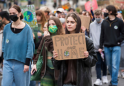 """© Licensed to London News Pictures; 22/10/2021; Bristol, UK. A young woman carries a placard saying """"protect our home"""" during a pre-COP26 Bristol Youth Strike 4 Climate protest takes place in the city centre. Students and staff from Bristol and Bath universities, colleges, and schools to protest inaction of governments globally, and about the lack of progress by Bristol City Council in tackling the climate and ecological crisis, on issues of clean air, Bristol airport expansion and climate justice. Photo credit: Simon Chapman/LNP."""