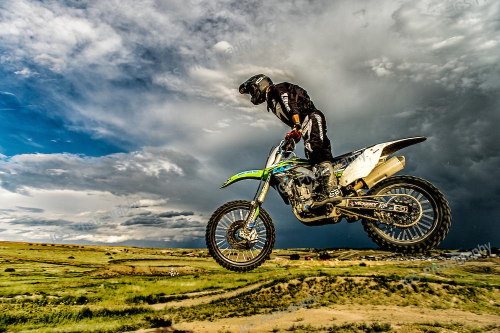 Motorcross rider airborne over jump at wild rat raceway