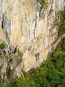 Tourists view the Inca Drawbridge, a back entrance to Machu Picchu. Aguas Calientes, Peru