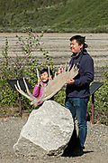 Asian visitors holds up a Moose antler during a stop at the Teklanika River in Denali National Park Alaska. Denali National Park and Preserve encompasses 6 million acres of Alaska's interior wilderness.