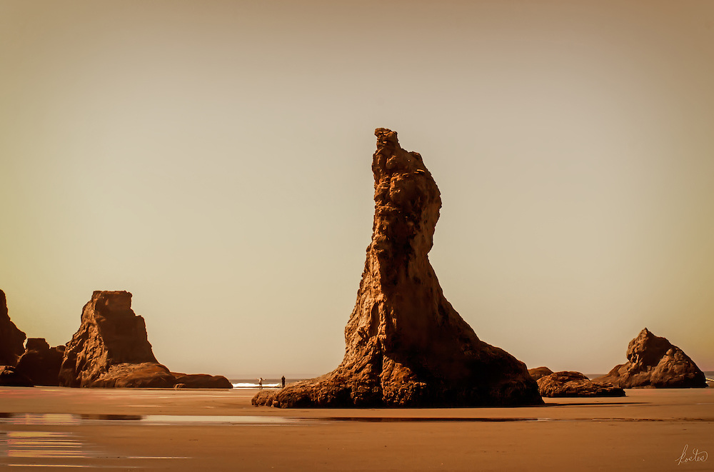 These wonderful rock formations are hard to believe. They are part of Bandon Beach on the Oregon coast. A nice little feature here is the woman at water's edge with her arms outspread to the cosmos.