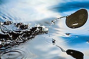 A rock skipping across the water's surface.