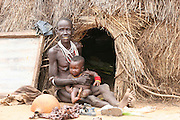Africa, Ethiopia, Omo Valley, Karo tribesmen woman and baby outside their hut