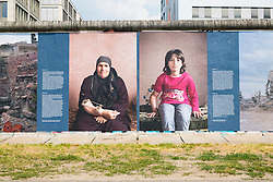 Images from War on Wall, a photography exhibition about war in Syria by Kai Wiedenhofer displayed outdoors on the Berlin Wall at East Side Gallery in Friedrichshain in Berlin Germany