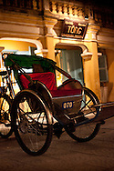 a rickshaw stands in a street of Hoi An, central Vietnam, in front of an old building, at night