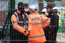 A man wearing a HS2 high-visibility jacket speaks to Karl Harrison (c) of the National Eviction Team during an operation to remove environmental activists from anti-HS2 campaign group HS2 Rebellion from tunnels beneath Euston Square Gardens on 6th February 2021 in London, United Kingdom. The activists entered tunnels dug by them beneath the site eleven days ago in order to seek to protect trees from felling in connection with the HS2 high-speed rail project.