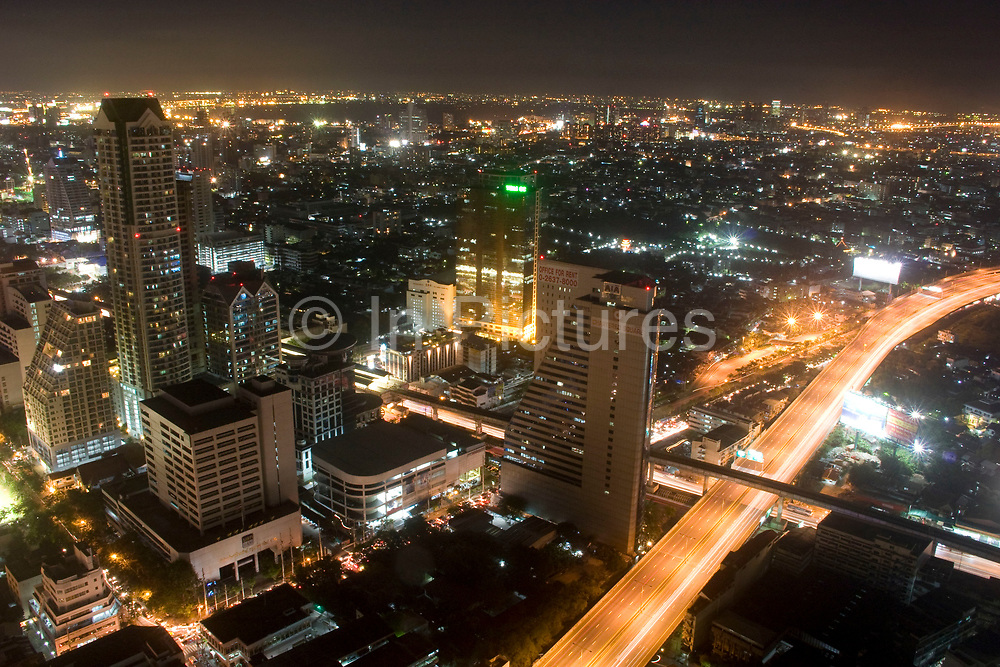 Night time Bangkok skyline viewed from the 54th floor of the Lebua Hotel at State Tower in Silom district. Cars run through the city on the expressways below, and Bangkok's status as an highrise giant of Asia is unquestionable.