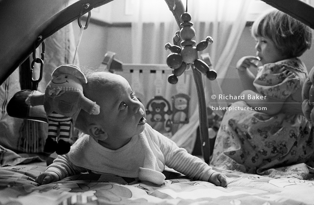 "A two and half year-old girl looks over her shoulder to eye her young baby brother suspiciously while he plays on the floor with a play mobile toy. It is bright from window light that shines down on the floor of their South London home where the two siblings play. Her brother is learning to lie on his front, using developing muscles in his neck and back to hold his head up towards a dangling toy. His sister enjoys having her own space and considers her innocent brother to be a little too close for her own comfort. From a personal documentary project entitled ""Next of Kin"" about the photographer's two children's early years spent in parallel universes. Model released."