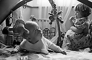 """A two and half year-old girl looks over her shoulder to eye her young baby brother suspiciously while he plays on the floor with a play mobile toy. It is bright from window light that shines down on the floor of their South London home where the two siblings play. Her brother is learning to lie on his front, using developing muscles in his neck and back to hold his head up towards a dangling toy. His sister enjoys having her own space and considers her innocent brother to be a little too close for her own comfort. From a personal documentary project entitled """"Next of Kin"""" about the photographer's two children's early years spent in parallel universes. Model released."""