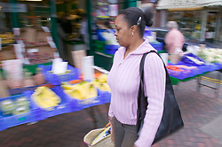 Woman out shopping passing a green grocers store,