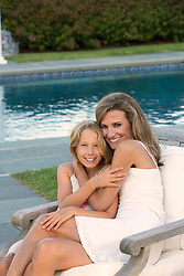 beautiful mother and daughter sitting outdoors in a chair by a swimming pool