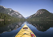 Kayaking on Ross Lake between the shadows of an unidentified peak at left and Pumpkin Mountain at right. In the saddle between is the Big Beaver Creek trail in the North Cascades National Park.<br /> Steve Ringman / The Seattle Times