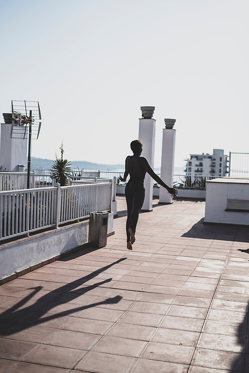 Sant Antoni de Portmany, Ibiza, Spain - August 3, 2018: Maria, from Madrid, leaps into the afternoon sunlight on the rooftop of an apartment building in Sant Antoni (San Antonio), Ibiza.