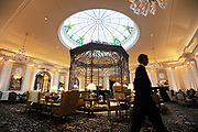 "A man walks through the Thames foyer of the Savoy Hotel in London. The iconic hotel reopened after a three year refit that cost £220 million ($350 million). The Savoy Hotel is a located on the Strand, in central London. Built by impresario Richard D'Oyly Carte the hotel opened on 6 August 1889. It was the first in the Savoy group of hotels and restaurants owned by Carte's family for over a century. It has been called ""London's most famous hotel"" and remains one of London's most prestigious and opulent hotels, with 268 rooms and panoramic views of London."