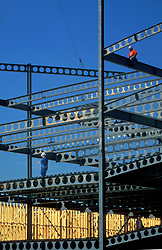 Stock photo of men walking on beams during a construction project