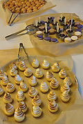 A buffet table laden with food. A dessert plate of sweet tartelettes (small tarts with various sweet fillings)