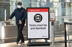 © Licensed to London News Pictures. 19/01/2021. London, UK. A traveller leaves a Covid-19 test centre in Heathrow Airport near London. Travel corridors in the the UK were closed at 04:00 hours on 18 January 2021 as British government declared. Travellers arriving to England from anywhere outside the UK have to to self-isolate for 10 days and must have proof of a negative coronavirus test. Photo credit: Ray Tang/LNP