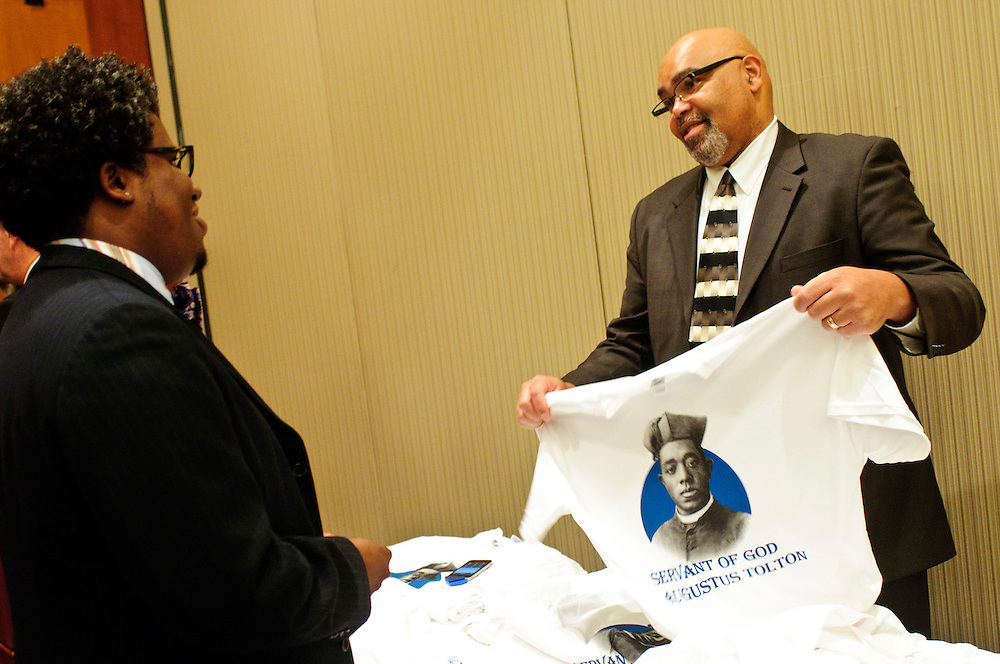 Marvin McCurry (L) chats with Andrew Lyke, Director of the Archdiocese of Chicago's Office for Black Catholics, as he folds a shirt designed for the Cause for Sainthood of Father Augustus Tolton during a Gala by the same title at the Hyatt Regency McCormick Place on Friday, October 19th, 2012. The event is co-sponsored by The Father Tolton Guild and the Office of Vicariate VI and Bishop Joseph Perry l Brian J. Morowczynski~ViaPhotos..For use in a single edition of Catholic New World Publications, Archdiocese of Chicago. Further use and/or distribution may be negotiated separately. ..Contact ViaPhotos at 708-602-0449 or email brian@viaphotos.com.   .The Archdiocese of Chicago's Office for Black Catholics hosts it's second annual Gala for the Cause for Sainthood of Father Augustus Tolton at the Hyatt Regency McCormick Place on Friday, October 19th, 2012. The event is co-sponsored by The Father Tolton Guild and the Office of Vicariate VI and Bishop Joseph Perry.