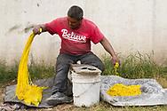 Un hombre trabaja al aire libre cortando mecha para cohetes.