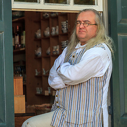 Costumed interpreter sitting in a window portrays a man colonist at Colonial Williamsburg, VA.