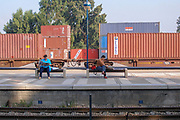Israel Rail. Hadera Train station. Cargo trains with containers are parked behind the platform