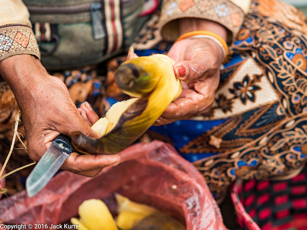 16 JUNE 2016 - PAKSE, CHAMPASAK, LAOS: A vendor cuts up lotus root in Dao Heuang Market, the largest market in Pakse. Pakse is the capital of Champasak province in southern Laos. It sits at the confluence of the Xe Don and Mekong Rivers. It's the gateway city to 4,000 Islands, near the border of Cambodia and the coffee growing highlands of southern Laos.      PHOTO BY JACK KURTZ