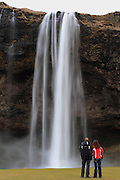 A couple look up at the Seljalandsfoss waterfall in Southern Iceland.