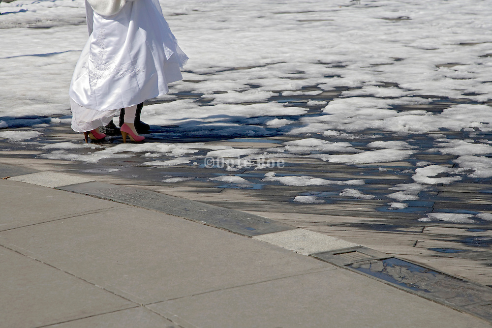 just married couple starting to walk over a snow covered boardwalk