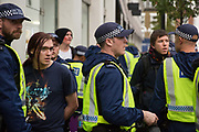 Metropolitan Police officers detain students who had been attending a National Demonstration for a Free Education on 4th November 2015 in London, United Kingdom. The demonstration was organised by the National Campaign Against Fees and Cuts NCAFC in protest against tuition fees and the Government's plans to axe maintenance grants with effect from 2016.