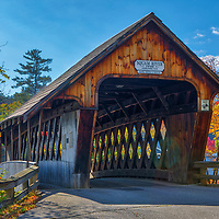 The iconic Squam River Covered Bridge in Ashland, New Hampshire framed by New England fall foliage.<br />
