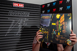 © Licensed to London News Pictures. 25/10/2021. LONDON, UK.  A DJ holds up the Ziggy Stardust album at the opening of a David Bowie pop-up shop in Heddon Street in the West End.  Open 75 days before the late singer's 75th birthday, the pop-up is located close to where Bowie posed as Ziggy Stardust on the cover of his 1972 album The Rise and Fall of Ziggy Stardust and the Spider from Mars.  The store sells limited edition records and memorabilia curated by his estate and will be open until January 2022. A sister shop will open in New York and both form part of a year long celebration of David Bowie's 75th birthday.  Photo credit: Stephen Chung/LNP