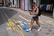 A muscular young man walks over multi-coloured aerosol-sprayed markings on the ground in a side-street off Long Acre near Covent Garden, are on 23rd June 2021, in Westminster, London, England.