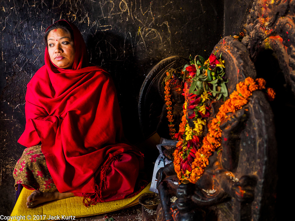 11 MARCH 2017 - KATHMANDU, NEPAL: A Buddhist woman solicits donations in a shrine at Swayambhu Stupa. The second most important Buddhist stupa in Kathmandu, Swayambhu Stupa is also a historic landmark and has panoramic views of Kathmandu. It is sacred to both Buddhists and Hindus. The stupa is being rebuilt because it was badly damaged in the 2015 earthquake.   PHOTO BY JACK KURTZ