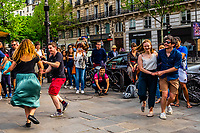 Two couples dancing on the sidewalk on Boulevard St. Germain des Pres, Latin Quarter, Paris, France.