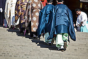 shinto priests walking up the stairs at the Tsurugaoka Hachimangu shinto shrine in Kamakura Japan