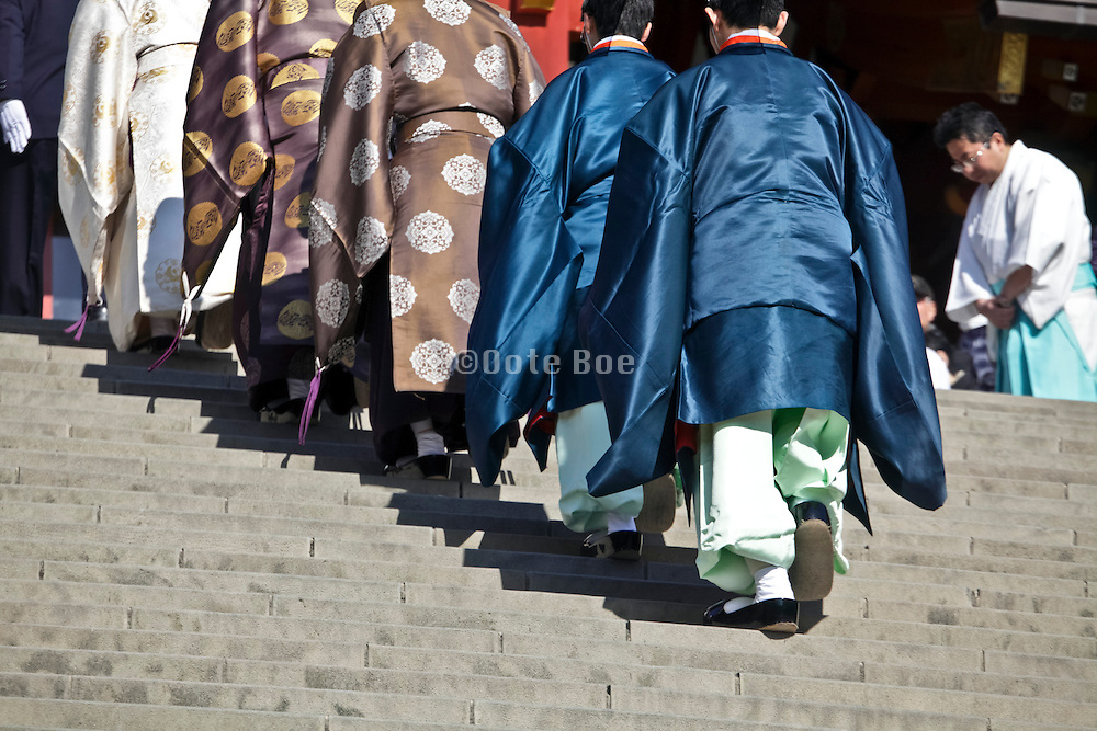 shinto priests walking up the stairs at the Tsurugaoka Hachimangu shinto shrine in Kamakura Japan