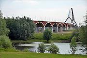 Nederland, Nijmegen, 2506-2015De stadsbrug van de stad Nijmegen, de Oversteek en de uiterwaarden van de Waal. Gebouwd door de aannemers BAM Civiel B.V. en Max Bogl Nederland B.V. De brug is vernoemd naar de heldhaftige oversteek van de rivier de Waal die Amerikaanse soldaten op dit punt maakten tijdens de operatie Market Garden in de tweede wereldoorlog om met succes de oude Waalbrug te veroveren. De overspanning is een belangrijke schakel in de ontlasting van de stad van het doorgaande verkeer. De Oversteek is een boogbrug van 285 meter lang en 60 meter hoog en is de op een na langste hoofd overspanning van Nederland, en de grootste boogbrug van Europa met een enkelvoudige boog. De nieuwe oeververbinding moet zorgen voor een betere spreiding en doorstroming van verkeer binnen de stad Nijmegen. Na 75 jaar is er eindelijk een tweede vaste verbinding voor de stad. De skyline van de stad is veranderd. De brug is een ontwerp van de Belgische architecten Ney en Paulissen. Foto: Flip Franssen/Hollandse Hoogte
