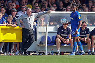 AFC Wimbledon manager Wally Downes leaning against the dugout whilst AFC Wimbledon defender Paul Kalambayi (30) takes a throw during the EFL Sky Bet League 1 match between AFC Wimbledon and Bristol Rovers at the Cherry Red Records Stadium, Kingston, England on 19 April 2019.