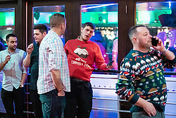 """© Licensed to London News Pictures . 21/12/2018 . Manchester , UK . A man wearing a Merry Christmas sweater slumps back against a window at the Printworks . Revellers out in Manchester City Centre overnight during """" Mad Friday """" , named for historically being one of the busiest nights of the year for the emergency services in the UK . Photo credit : Joel Goodman/LNP"""
