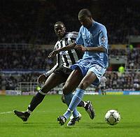 Photo. Glyn Thomas, Digitalsport<br /> Newcastle United v Tottenham Hotspur. FA Barclaycard Premiership. St James' Park, Newcastle. 13/12/2003.<br /> Newcastle's Shola Ameobi (L) is held back by Anthony Gardner.
