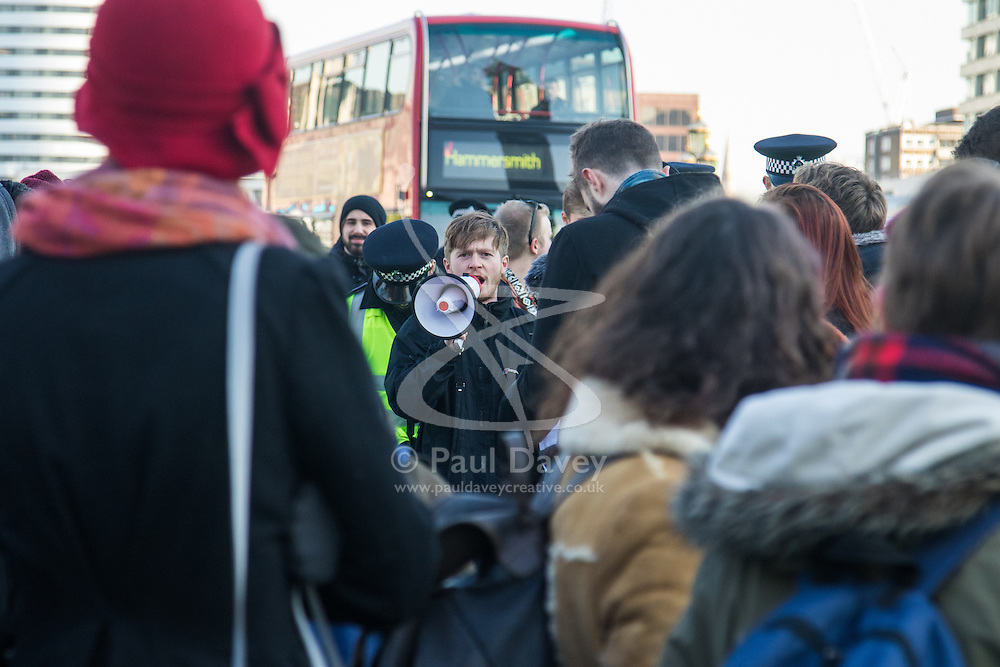 """Westminster, London, January 19th 2016. Students hold an """"emergency protest"""" in Parliament Square and later blocking Westminster Bridge, against the cutting of maintenance grants. """"It took just 18 MPs 90 minutes to scrap maintenance grants for the million poorest students, without a debate in Parliament in a backroom committee"""" PICTURED: A protester uses a loudhailer to lead chants of """"No grants, no bridge!"""". ///FOR LICENCING CONTACT: paul@pauldaveycreative.co.uk TEL:+44 (0) 7966 016 296 or +44 (0) 20 8969 6875. ©2015 Paul R Davey. All rights reserved."""