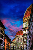 """""""The ancient and the modern compete for a piece of heaven in Florence""""…<br /> <br /> Santa Maria del Fiore (also known simply as the Duomo) is the cathedral of Florence known for its distinctive Renaissance dome. Its name (""""Saint Mary of the Flower"""") refers to the lily, the symbol of Florence. The impressive Gothic cathedral complex includes the Duomo, the famous baptistery, and a campanile. Built-in 1294 to be the largest Roman Catholic Church in the world, it is still the largest masonry dome in the world. Walking down the Strada, and turning the corner to view the massive Duomo painted against the sky was captivating. I stopped in my tracks and began taking photos; however, the huge Florence crowds prevented most images from ground level. This was one of the first images I photographed noticing the ancient architecture of the Duomo competing across the narrow Strada with the more modern buildings of Firenze as colorful evening skies danced above."""