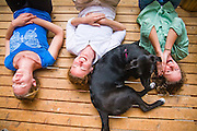 A dog snuggles with three women lying down on a porch at a cabin outside Leavenworth, Washington.