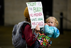 © Licensed to London News Pictures. 04/02/2017. London, UK. A woman carrying her daughter holds up a sign as Thousand of protestors take part in a demonstration against U.S President Donald Trump's Executive Order banning refugees and immigrants from a number of Muslim-majority countries. Protestors join campaign groups including Stop the War, Stand up to Racism, Muslim Association of Britain, in a march from the U.S Embassy in London to Downing Street. Photo credit: Ben Cawthra/LNP