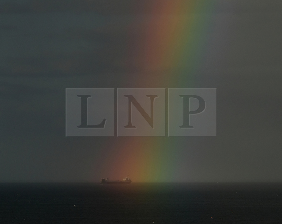 © Licensed to London News Pictures. <br /> 01/08/2017. <br /> Saltburn by the Sea, UK.  <br /> <br /> A rainbow appears to rise from a ship as it heads along the coast to Teesport.<br />   <br /> Photo credit: Ian Forsyth/LNP