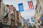 During the UK's Coronavirus pandemic lockdown and on the day when a further 255 deaths occurred, bringing the official covid deaths to 37,048, <br /> Union Jack flags and banners thanking NHS (National Health Service) key workers hang above fashion retailers and art galleries on New Bond Street, on 26th May 2020, in London, England.
