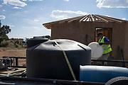 CB Barton fills water barrels at a hogan under construction in the Navajo, Nation near Gallup, New Mexico.