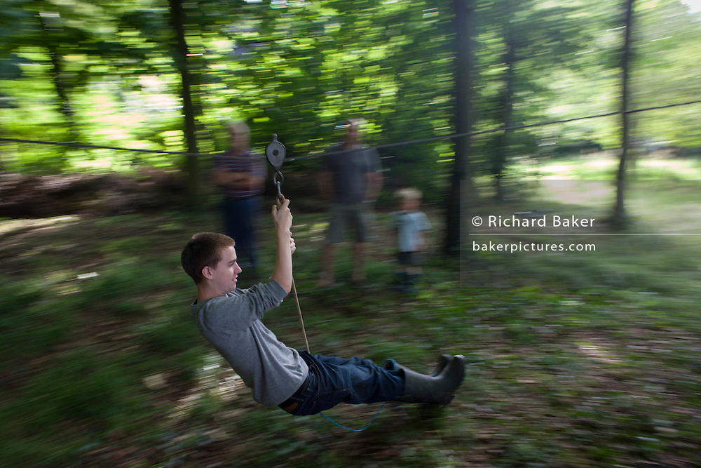 A 15 year-old boy blurs across woodland during a home-made zip wire ride on private land in Somerset. The young lad keeps his legs straight to avoid scraping them along the woodland floor and stopping him before the end of the short ride. In the background are members of his family of varying ages, encouraging and laughing as he sweeps past on this bright summer afternoon.