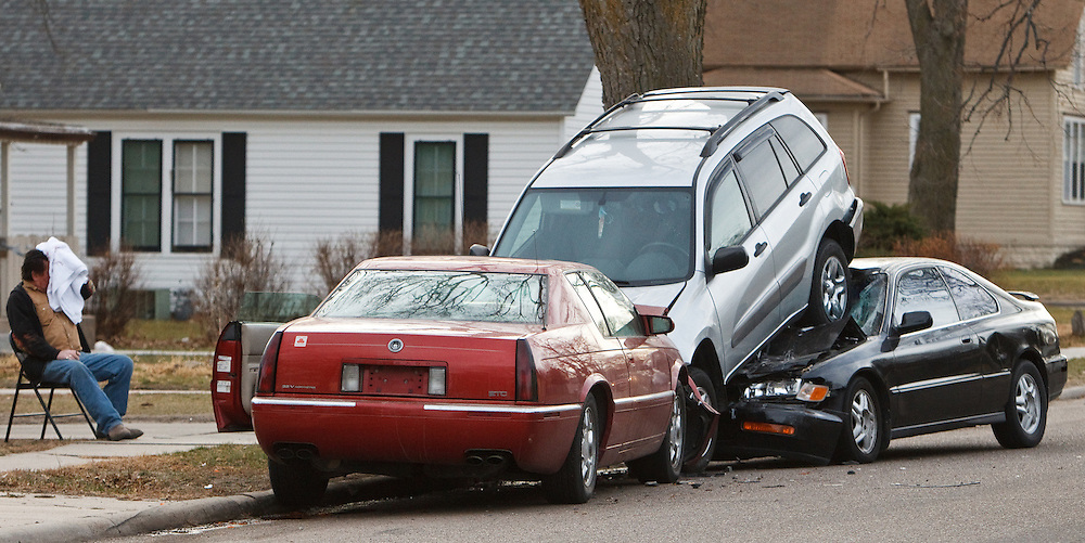 Harold Carey, 67, holds a towel to his head after crashing his 1997 Cadillac El Dorado into a parked 2005 Toyota RAV4, pushing it on top of a 1997 Honda Accord Wednesday on Charles Street between Cedar and Elm Streets in Grand Island. According to police, Carey was driving westbound on Charles when he reached for some items in his car causing his attention to be diverted long enough that his vehicle hit the parked cars. The accident report said that Carey was not wearing a seat belt and it said that he reported that he might have blacked out briefly after the accident. As a result, Carey was transported to the hospital, where it was reported that he was treated and released. (Independent/Matt Dixon)